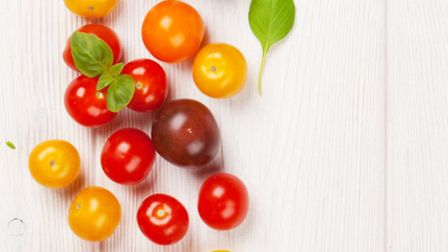 Ripe and colourful tomatoes with a hint of basil © Fotolia