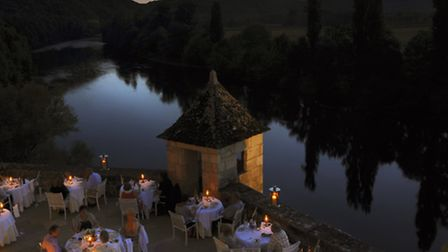 Guests enjoy dinner out on the hotel's riverside terrace