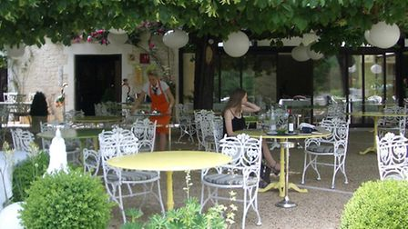 A customers relaxes on Le Pont de l'Ouysse's terrace underneath a spreading sweet chestnut tree
