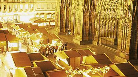 Rows of quaint Christmas market stalls sparkle in the winter lights outside the soaring Notre-Dame c
