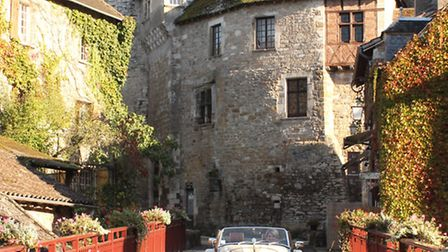 Carolyn Boyd at the wheel of the Morgan sports car in the Plus Beau Village of Carennac on the banks