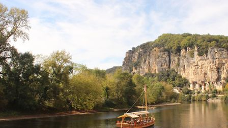 A gabare barge sails serenely along the River Dordogne at La Roque-Gageac