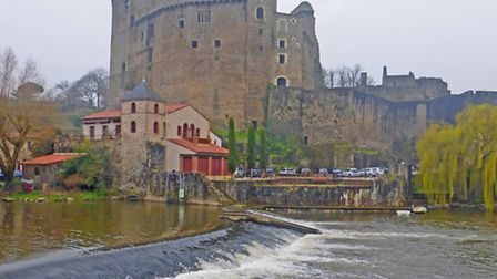 The old castle clings to the riverbank in Clisson