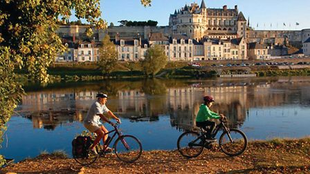 Cyclists pass through the town of Saumur on the Loire à Vélo