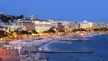 Evening lights gleam on Cannes' famous Croisette, so-named for its crescent shape