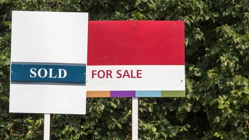 'For Sale' and 'Sold' signs outside a property in the UK