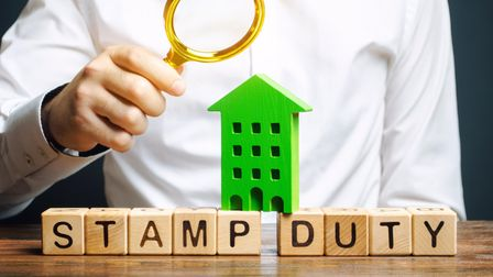 Businessman puts wooden blocks with the word Stamp duty and house. Taxes assessed during the transfe
