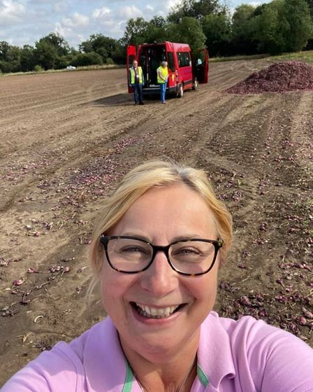 Community Hub Co-Ordinator at FACT, Nicola Christy, collecting red onions from a field with volunteers.