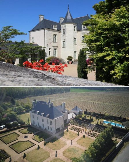 A French château with white walls and grey pointed roof surrounded by gardens and vineyards