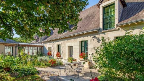 Loire Valley property built in pale stone. In front a table and chairs sits on the patio surrounded by roses.