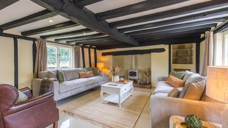 Large living room with timber ceiling and inglenook fireplace in this 6-bed farmhouse for sale in Larling, Norfolk