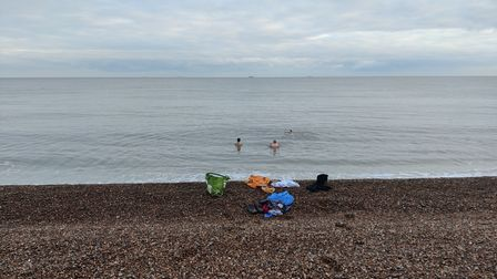People swimming in the north sea off a shingle beach