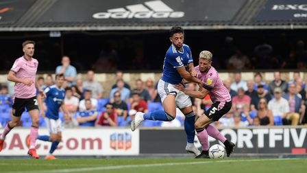 Macauley Bonne is stopped in his tracks by a strong challenge at Portman Road against Sheffield Wedn