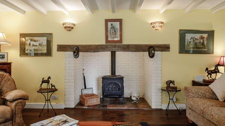 Large brick hearth in a sitting room in this 4-bed £1.45m property for sale in Stow Bedon near Thetford Forest