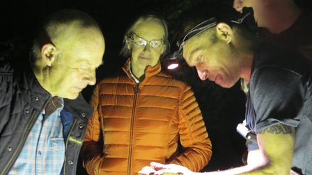 Moth spotters examine a small creature in a man's hand at Great Dunmow's moth night