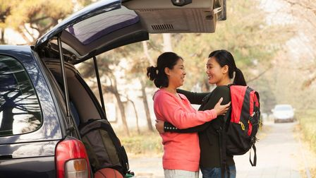 Mother and daughter hugging as they load up boot of car