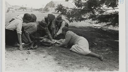 Mercie Lack showing members of the excavation team a selection of contact prints, with the excavation in the background