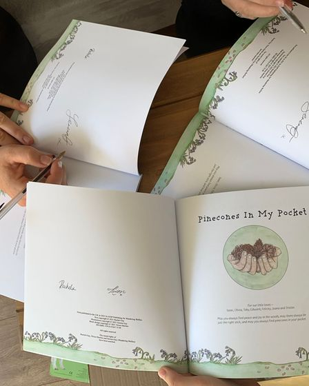 Copies of Pinecones In My Pocket being signed