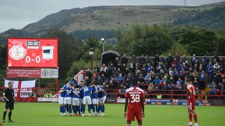 Town players in a pre-match huddle against the backdrop of the hills around Accrington.