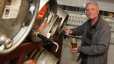 James Potter pours a beer from one of the casks at the Artichoke pub in Broome