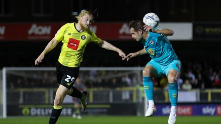 Harrogate Town's Luke Armstrong (left) and Newport County's Matthew Dolan battle for the ball during