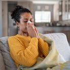 A woman at home on her sofa blowing her nose