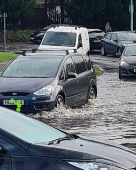 Vehicles fording a puddle in sudbury