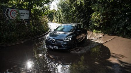 A car turning a bend in a puddle