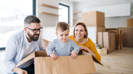 A portrait of happy young family with a toddler girl moving in new home.