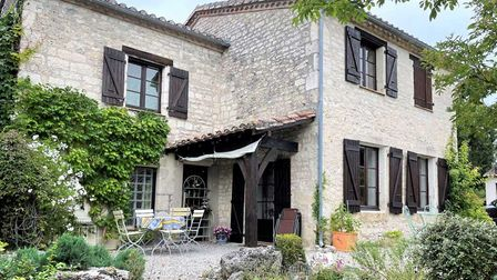 Stone house with wooden shutters and climbing vines