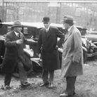Henry Ford stands with three other man beside parked cars