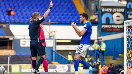 Scott Fraser is show the yellow card by referee Will Finnie after going down in the penalty area.
