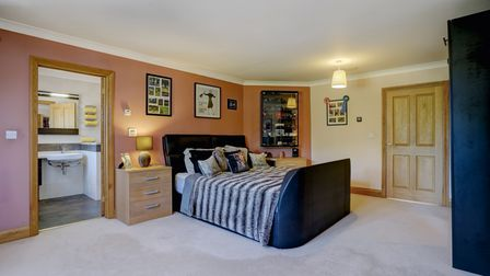 Large double bedroom with open door to en suite in this £1.4m equestrian property for sale in Rollesby, Norfolk