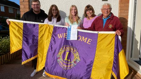 five people in a line holding a flag