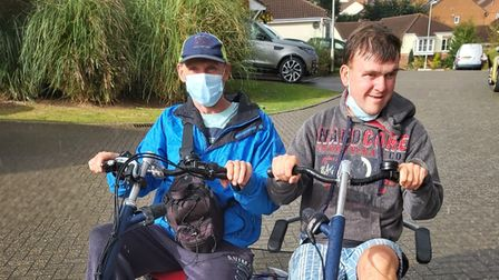 Two men in a specially adapted side by side bicycle