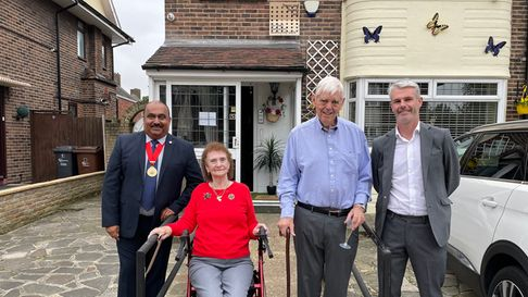 Four people outside a home