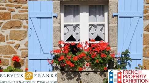 Blue shutters and red flowers frame a French property