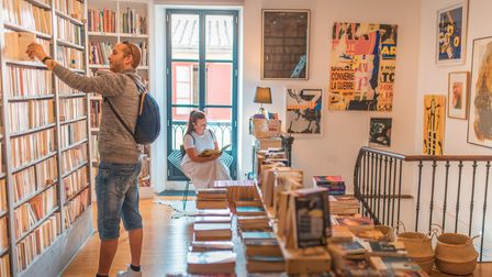A man browses the shelves in a bookshops in Montolieu, Aude, while a woman sits by a window reading her chosen book