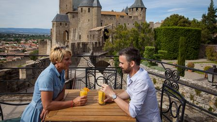 A man and a woman drink orange juice next to a wrought iron fence on a terrace in front of a turreted French castle