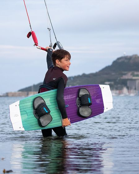 Young kitesurfer in the sea with his board