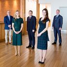 Five business people in smart clothes standing on a wooden floor