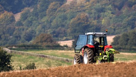 Agricultural tractor ploughing a field in a rolling English landscape