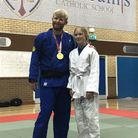 A man with a gold medal standing with a girl, both wearing uniforms