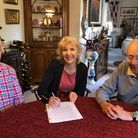 Gareth Cole and Shirley Moore of Sudbury Hive sign the contract to buy the former church with John Smith as a witness