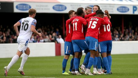 Sam Ling of Dagenham and Redbridge scores the third goal for his team and celebrates with his team m