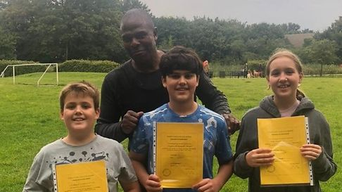 Three children holding certificates with a man standing behind them in a park