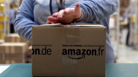 A worker tapes shut a parcel in the Amazon fulfilment centre in Peterborough Cambridgeshire. Picture