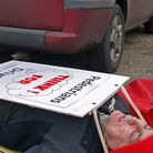 """Norman Hart, chairman of Harleston's Future, being """"run over"""" by Carol Wiles to promote the road saf"""
