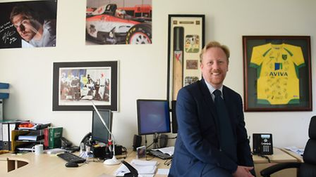 Dan Chapman, senior partner at Full Contact sports agency, in his office with signed photographs and