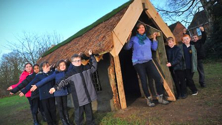 Happier times: Builder Kate Edwards with pupils and the finished longhouse at West Earlham Junior Sc